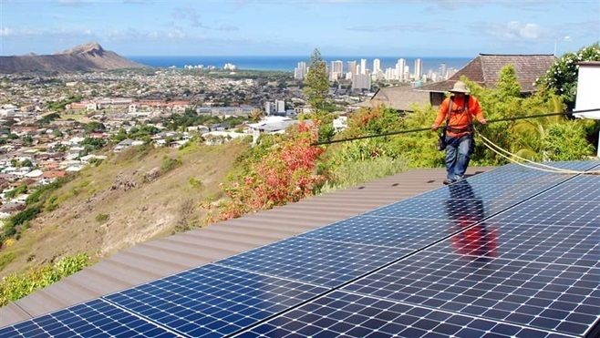 A worker installs solar panels on a roof in Honolulu. More states will encourage the use of renewable energy this year, seein