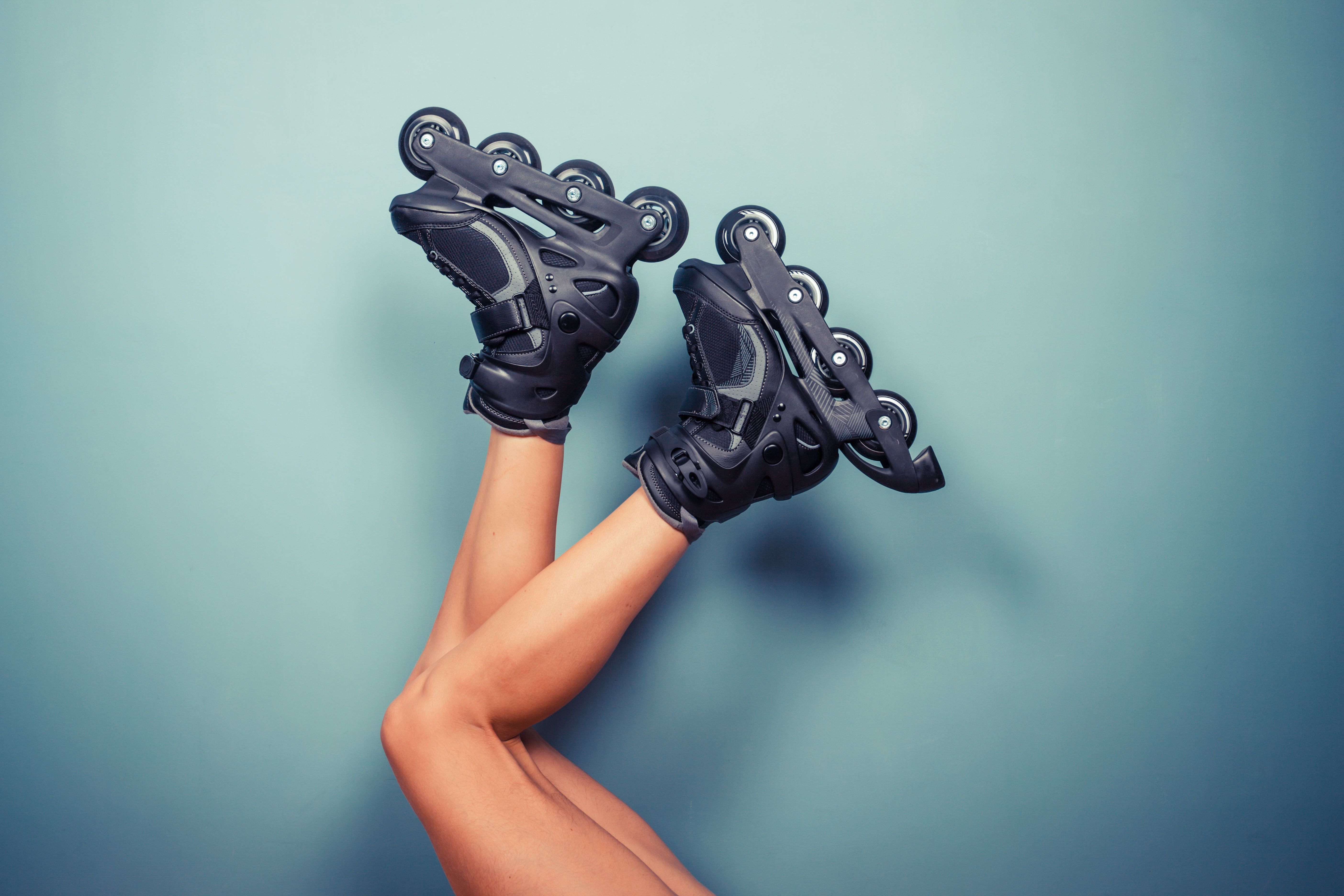 The legs of a young woman wearing rollerblades