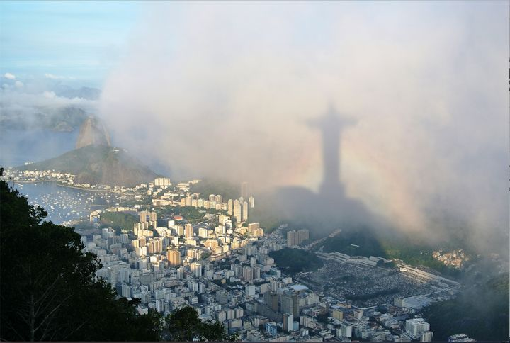 "Location:&nbsp;Corcovado, Rio de Janeiro.&nbsp;<br /><br />""... Suddenly, the clouds parted to reveal Rio de Janeiro in all its glory and I quickly set up my camera. As light flooded across the city, I noticed the shadow of Christ the Redeemer fill my frame and quickly took a series of shots, as a rainbow briefly gave the statue its own halo.""&nbsp;"