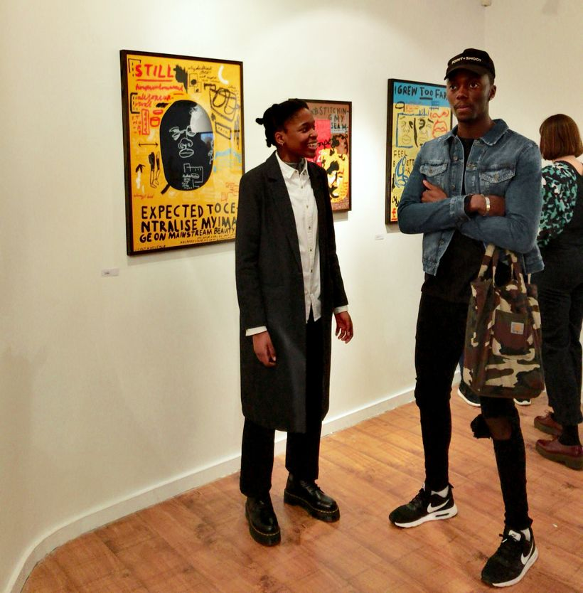 Artists Joy Miessi and Emmanuel Unaji in front of Miessi's series of illustrations on display at Mission Gallery's <em>Ain&#3