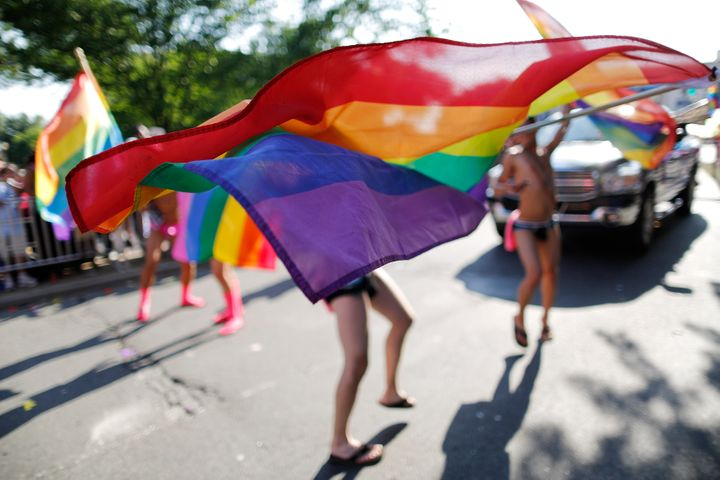 Men dance with rainbow flags as they take part in the Capital Pride Parade in Washington on June 8, 2013.