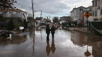 NEW YORK, NY - NOVEMBER 02:  Neighbors speak in a flooded street on November 2, 2012 in the Staten Island borough of New York City. Hundreds of thousands of people in Staten Island remained without electricity in areas affected by the superstorm.  (Photo by John Moore/Getty Images)