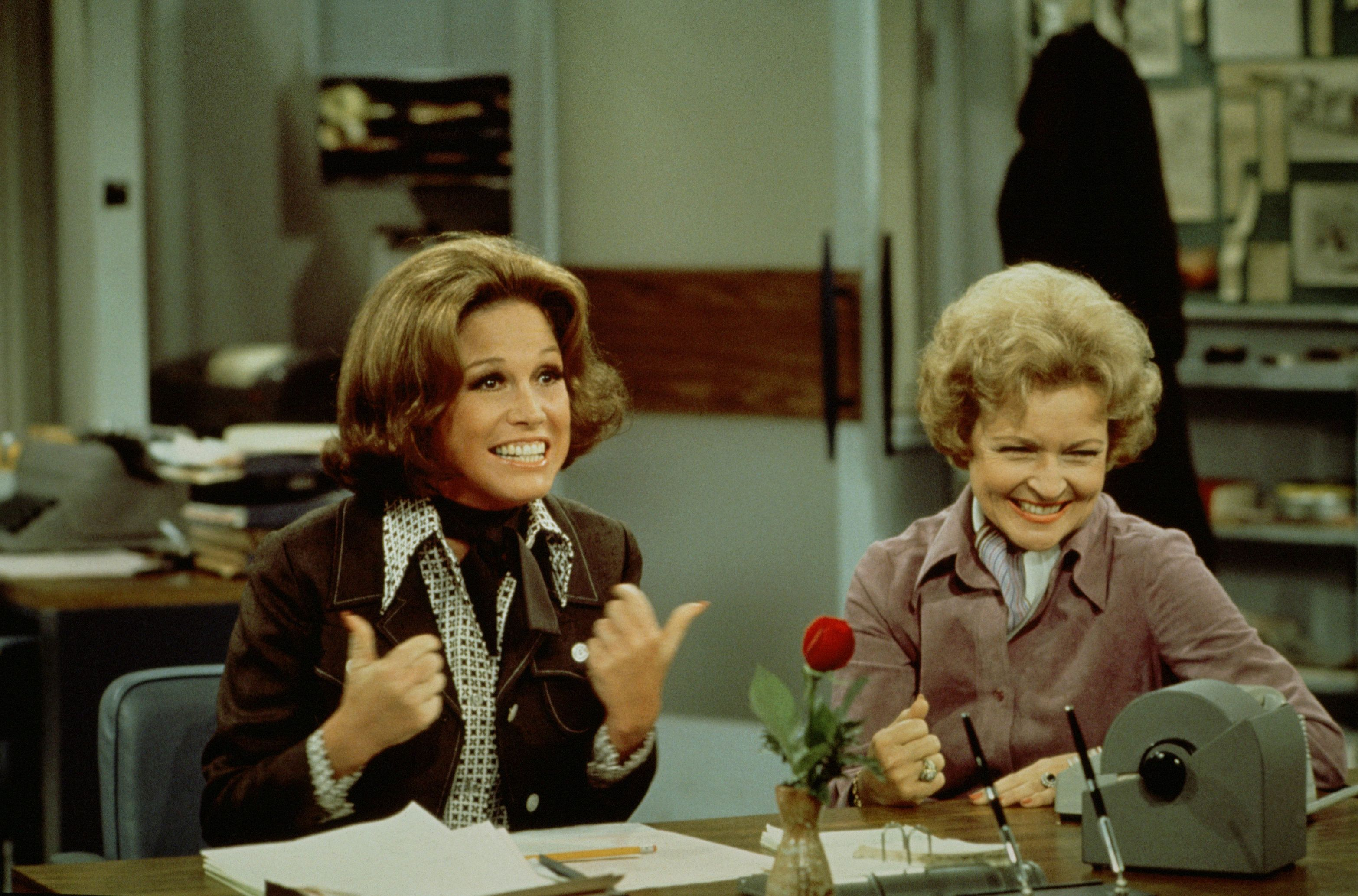 American actress Mary Tyler Moore (as Mary Richards) (left) gives a 'thumbs up' sign as she sits at her desk with Betty White (as Sue Ann Nivens) in a scene from 'The Mary Tyler Moore Show' (also known as 'Mary Tyler Moore'), Los Angeles, California, 1975. (Photo by CBS Photo Archive/Getty Images)