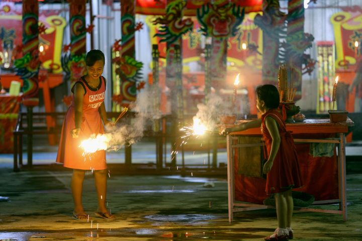 Malaysian-Chinese children play with firecrackers inside the temple ahead of Lunar New Year of the Rooster celebrations outsi