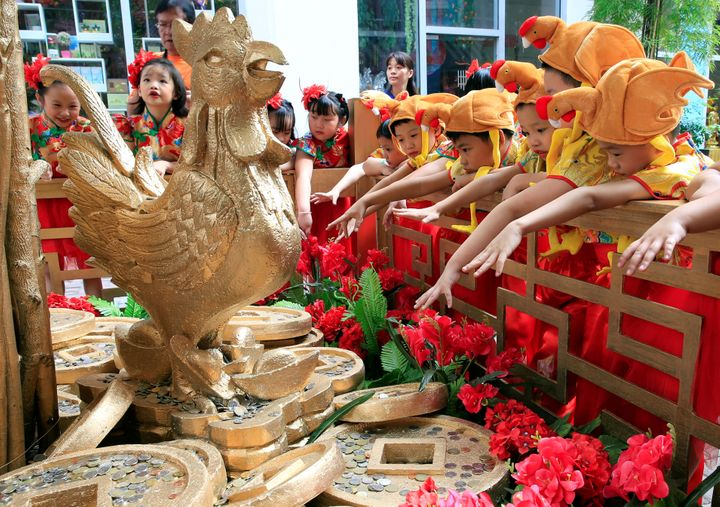 Filipino-Chinese students with rooster hats gesture after tossing a coin in front of a Prosperity Tree display, which is beli