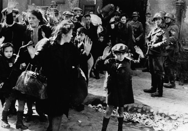 Frightened Jewish families surrender to Nazi soldiers at the Warsaw Ghetto in