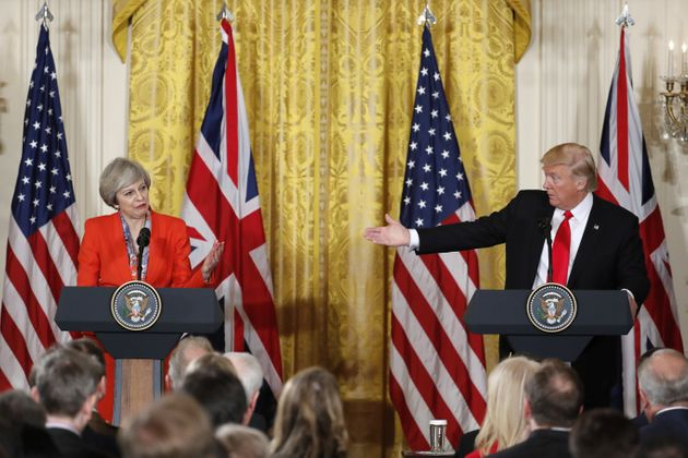 President Donald Trump gestures toward British Prime Minister Theresa May during their news conference...