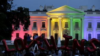 "People stand in front of the rainbow-colored illuminated White House with balloons that say ""Love Wins""after today's historic Supreme Court ruling legalizing gay marriage in Washington June 26, 2015.    REUTERS/Gary Cameron"