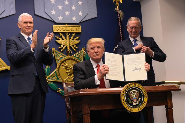 President Donald Trump shows his signature on executive orders alongside Defense Secretary James Mattis and Vice President Muike Pence on January 27, 2016 at the Pentagon in Washington, DC.