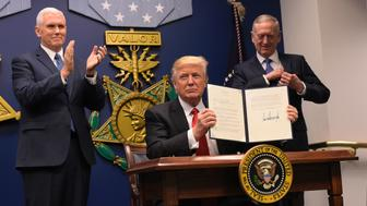 US President Donald Trump shows his signature on executive orders alongside US Defense Secretary James Mattis and US Vice President Muike Pence on January 27, 2016 at the Pentagon in Washington, DC. Trump signed an order Friday to begin what he called a 'great rebuilding' of the US armed services, promising new aircraft, naval ships and more resources for the military. 'Our military strength will be questioned by no one, but neither will our dedication to peace. We do want peace,' Trump said in a ceremony at the Pentagon.  / AFP / MANDEL NGAN        (Photo credit should read MANDEL NGAN/AFP/Getty Images)