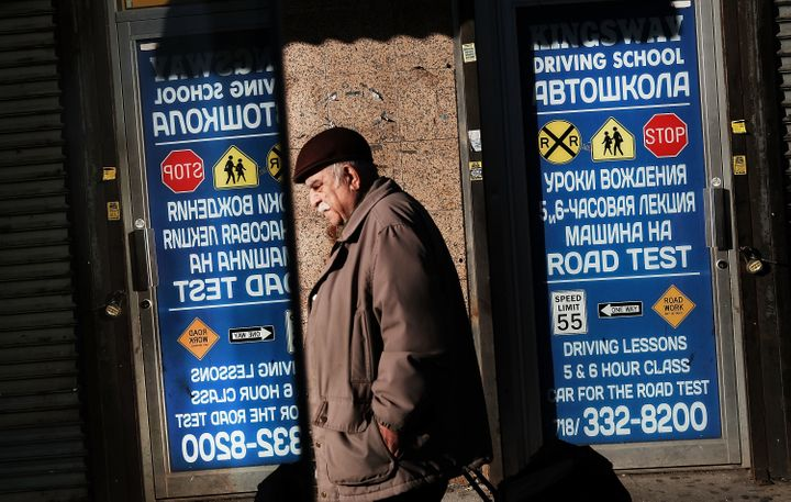 A man walks by signs in Cyrillic text in Brighton Beach, Brooklyn.