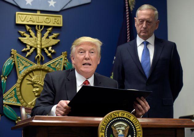 President Donald Trump, left, with Defense Secretary James Mattis, right, watching, explains the executive...
