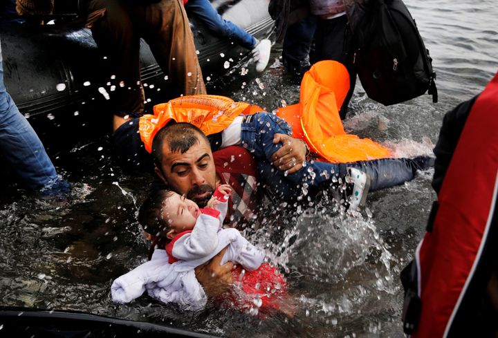 A Syrian refugee holds his two children as he struggles to disembark from a raft on the northern coast of the Greek island of