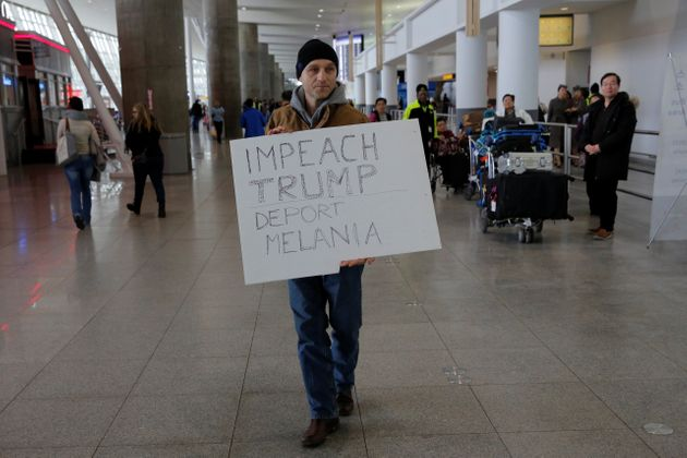 A protester walks through Terminal 4 at John F. Kennedy International Airport in Queens, New York, U.S.,...
