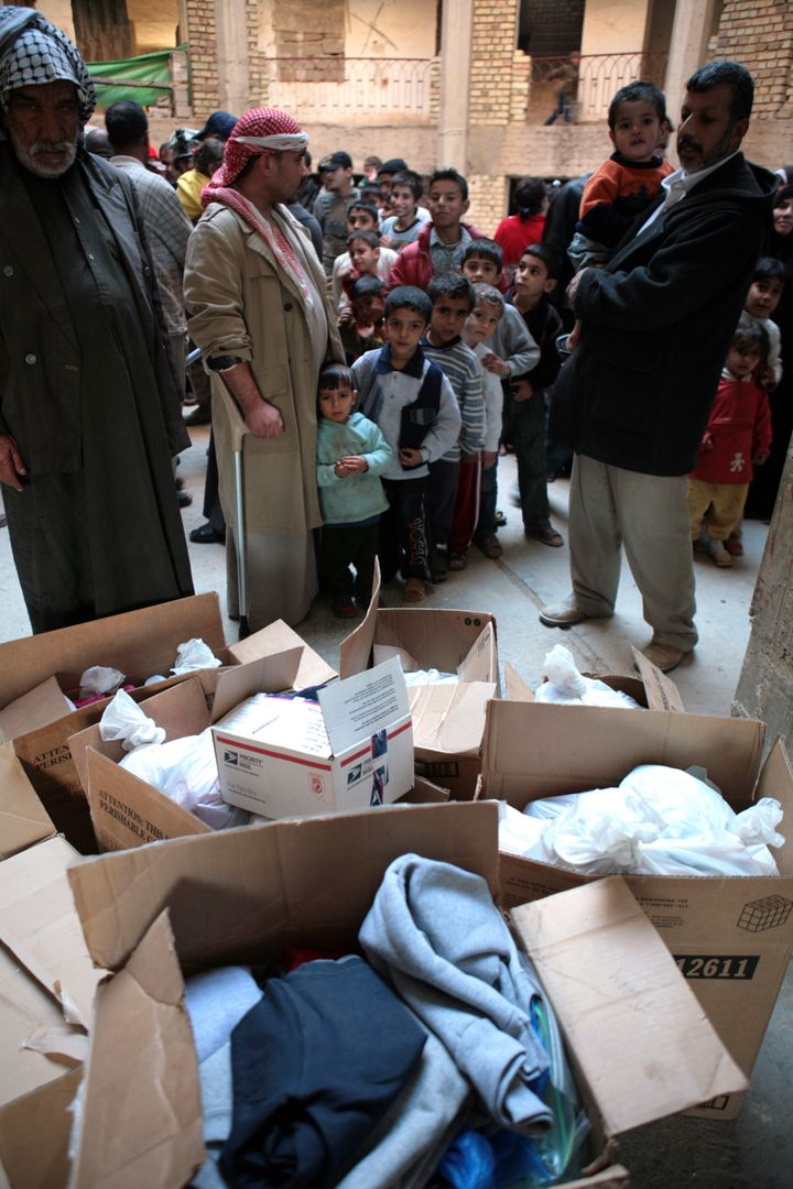 Iraqi refugees wait for presents from US Marines and Iraqi Policemen