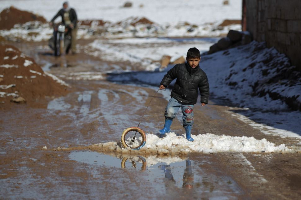 A boy plays with a wheel on snow in al-Rai town on Jan. 28.
