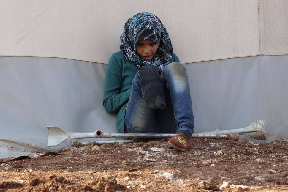 An internally displaced Syrian girl with an amputated leg checks her phone at the Bab Al-Salam refugee camp, near the Syrian-