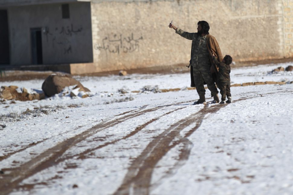 A rebel fighter takes a selfie with a boy on snow-covered ground in al-Rai town in the northern Aleppo countryside on Jan. 28