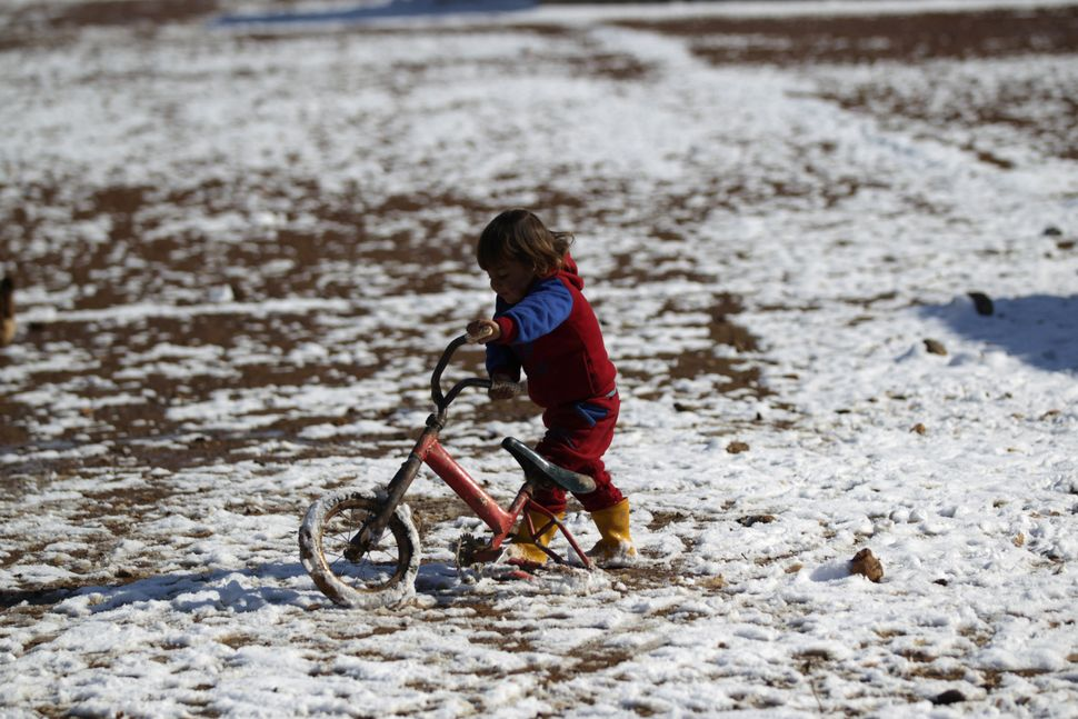 A child plays with a broken bicycle on snow in al-Rai town on Jan. 28.