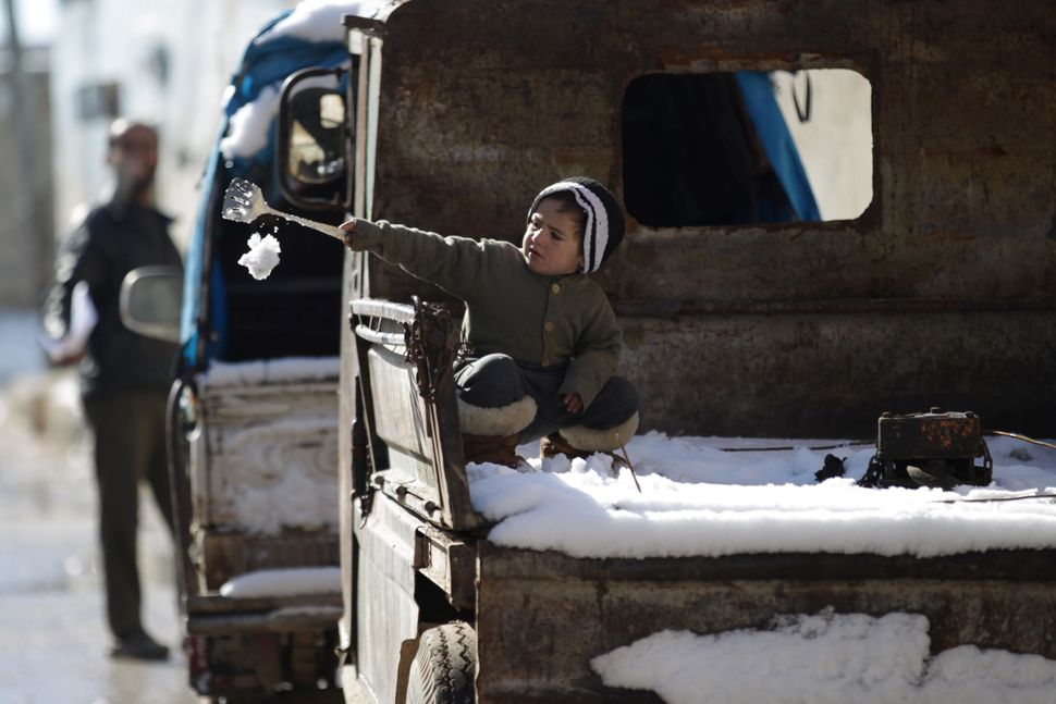A child plays with snow on the back of a pick-up truck in al-Rai town on Jan. 28.
