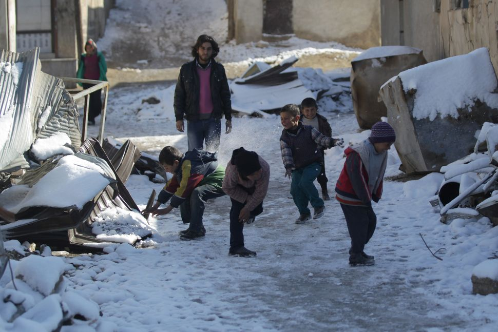 Children play with snow near the rubble of damaged buildings in al-Rai town on Jan. 28.