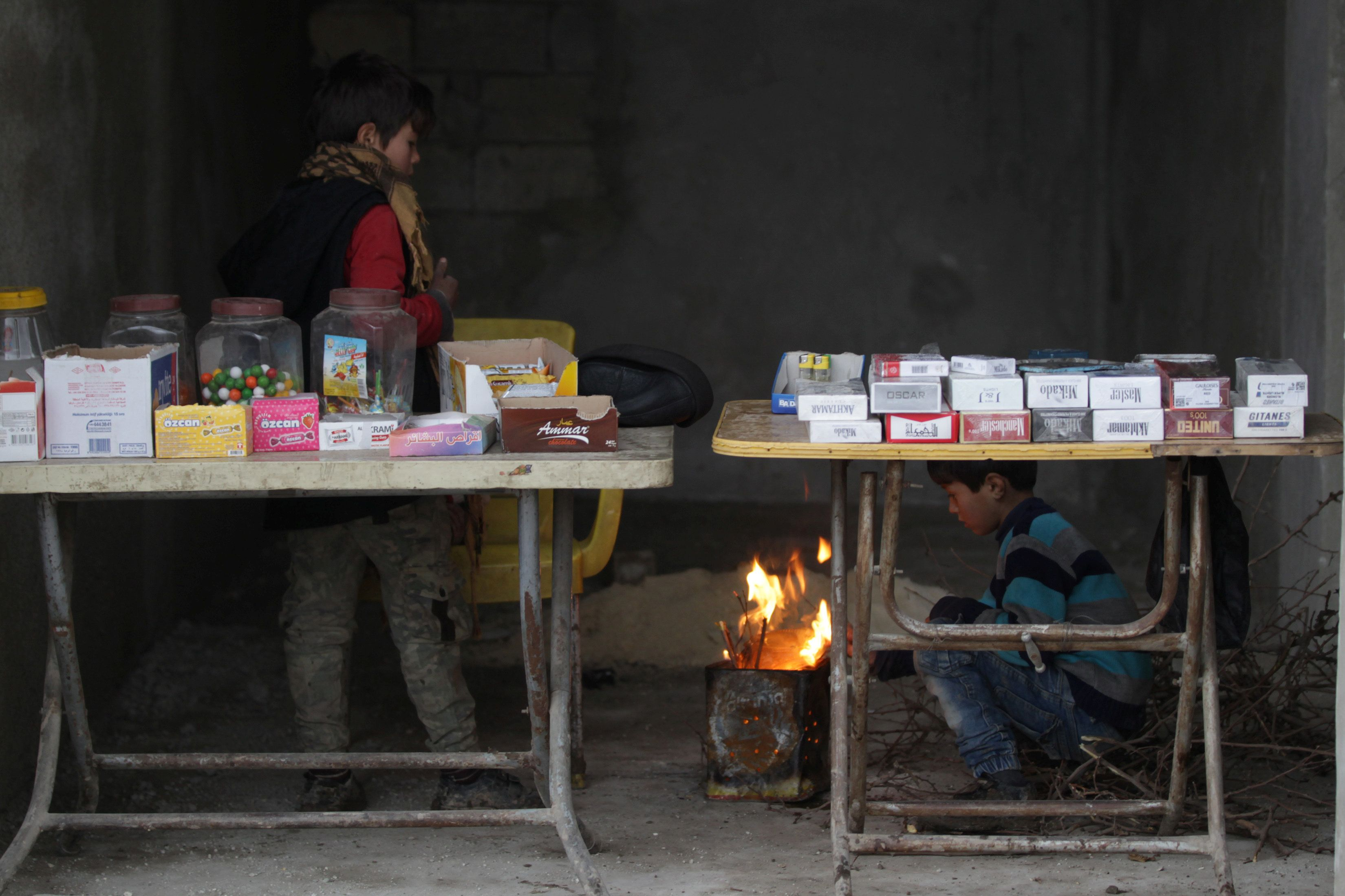 Children warm up by the fire near goods displayed for sale in al-Rai town on Jan. 27.