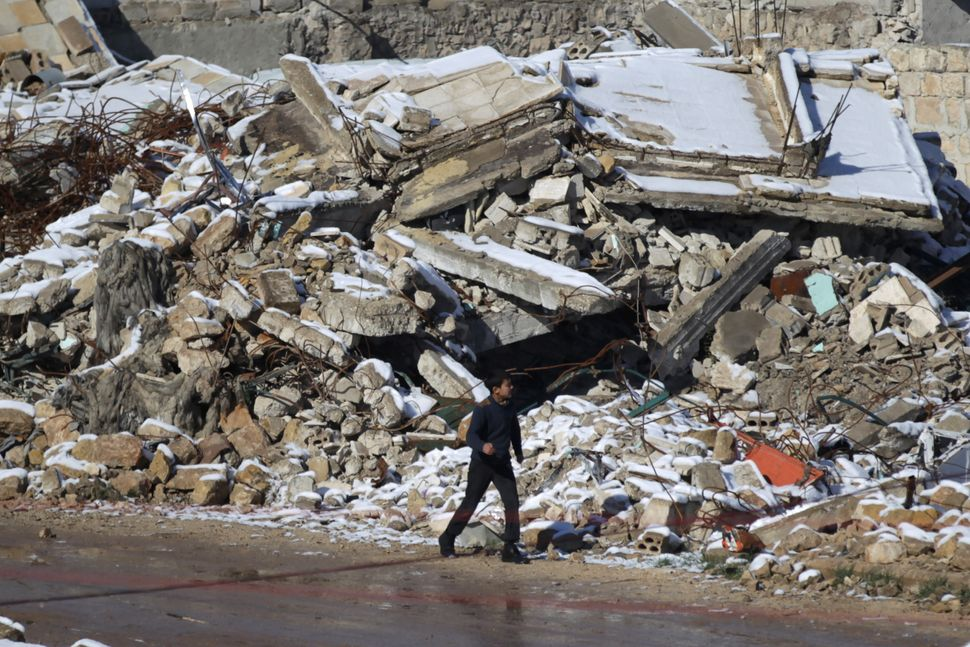 A boy walks near the snow-covered rubble of damaged buildings in al-Rai town on Jan. 28.
