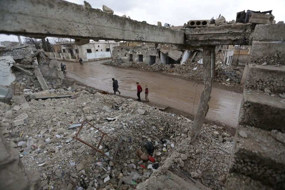 People walk past damaged buildings in al-Rai town on Jan. 27.