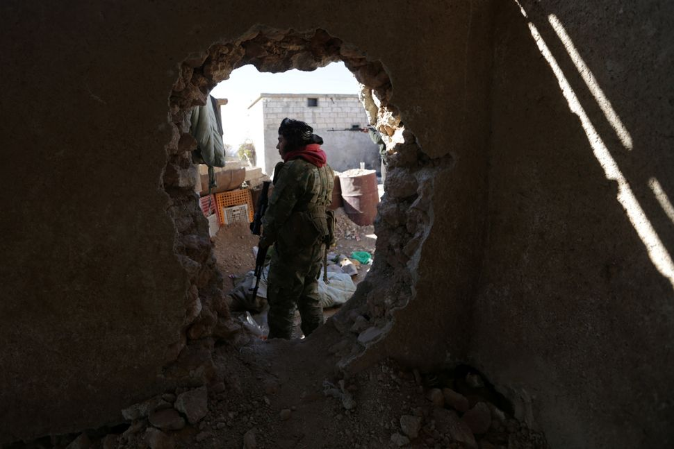 A rebel fighter carrying his weapon stands near a hole in a wall on the outskirts of al-Bab town in Aleppo on Jan.