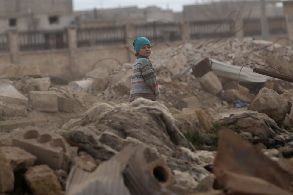 A child walks through the rubble of damaged buildings in al-Rai town on Jan. 20.