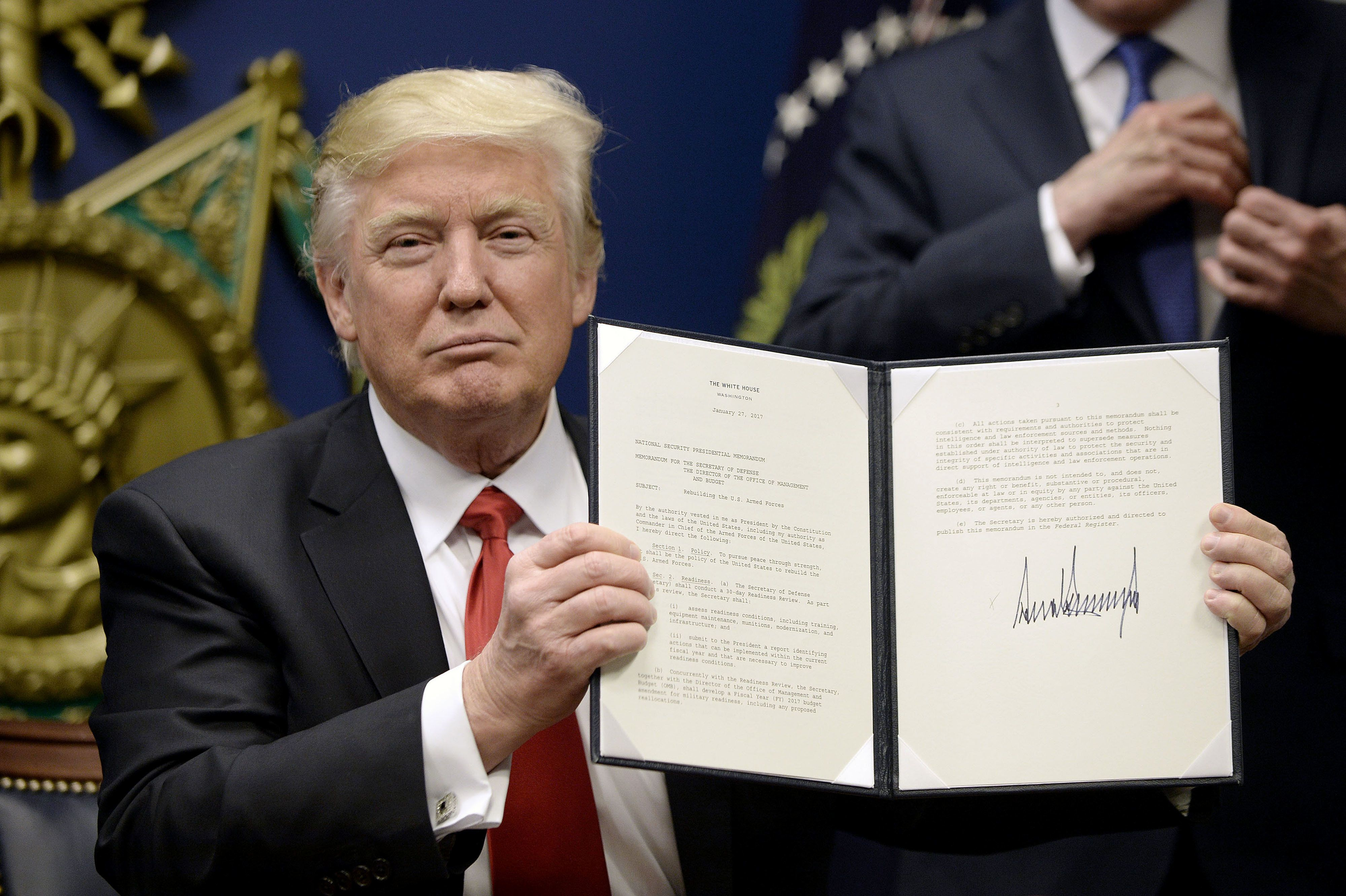 U.S. President Donald Trump holds up signed executive orders in the Hall of Heroes at the Department of Defense in Arlington, Virginia, U.S. on Friday, Jan. 27, 2017. Trump signed an executive action on Friday to establish new vetting procedures for some people seeking to enter the U.S., saying the measure would prevent terrorists from being admitted into the country. Photographer: Olivier Douliery/Pool via Bloomberg