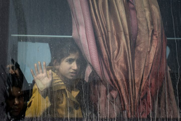 A young girl looks out a bus window for members of her family after fleeing fighting in Mosul, Iraq on Nov. 7, 2016