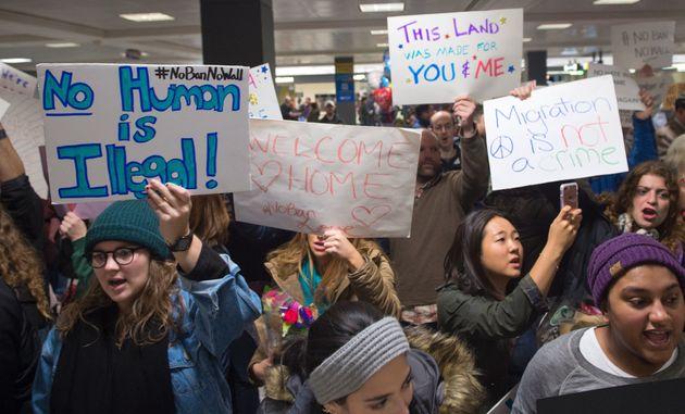People gather at the international arrivals area ofWashington Dulles International Airport on Jan....