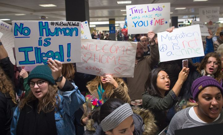 People gather at the international arrivals area of Washington Dulles International Airport on Jan. 28 to show their sup