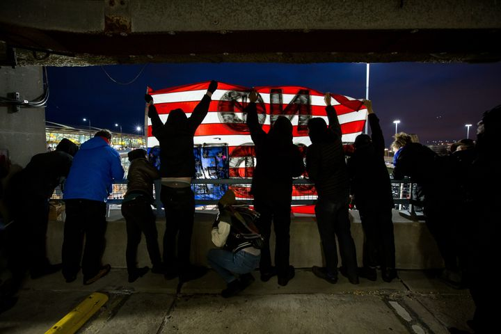 "Demonstrators in a parking garage at JFK hold an upside-down American flag saying ""no borders."""