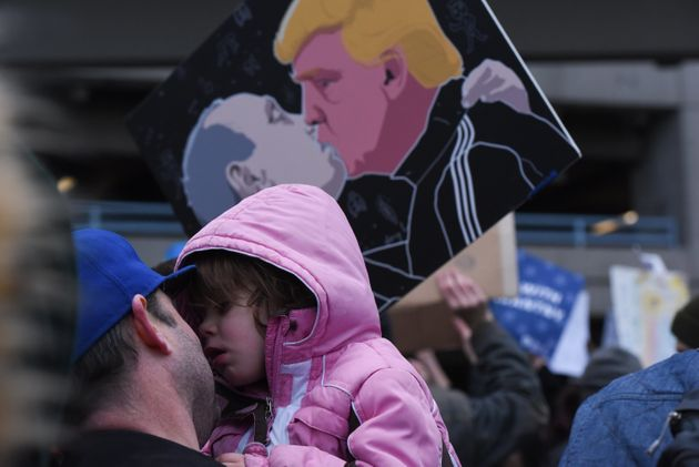 A man holds a child in front of a protest sign showing Donald Trump kissing Russian President Vladimir