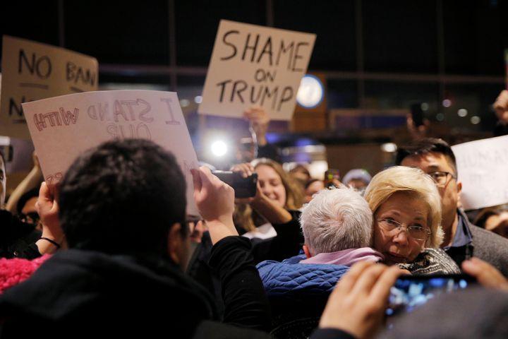 Massachusetts Sen. Elizabeth Warren (D) greets demonstrators at Logan Airport in Boston.