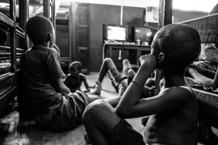 Kids, rescued from the streets of Bangui, watch a Nigerian soap opera in their dorm room.