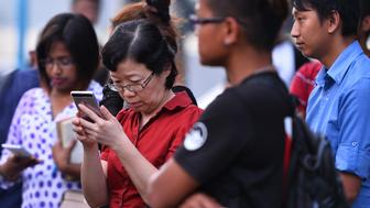 Chen Peijie (2nd L), China's consul-general in Sabah, checks her mobile phone at a jetty in Kota Kinabalu in the Malaysian Borneo state of Sabah on January 29, 2017, as she awaits developments after a tourist boat carrying 28 Chinese nationals was reported missing on January 28.    The skipper and a crewman from a tourist boat that went missing off Malaysia were found alive on January 29 but an air and sea search was continuing for some 28 Chinese passengers. / AFP / STR / Malaysia OUT        (Photo credit should read STR/AFP/Getty Images)