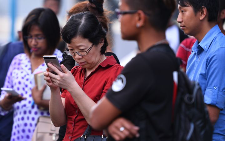 Chen Peijie (2nd L), China's consul-general in Sabah, checks her mobile phone at a jetty in Kota Kinabalu in the Malaysian Bo
