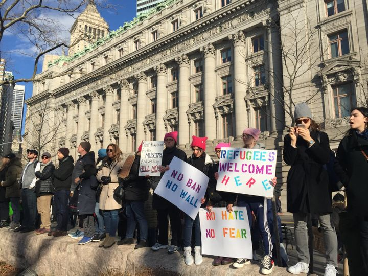 "Protesters carried signs reading ""Refugees welcome here"" and ""No hate, no fear."""