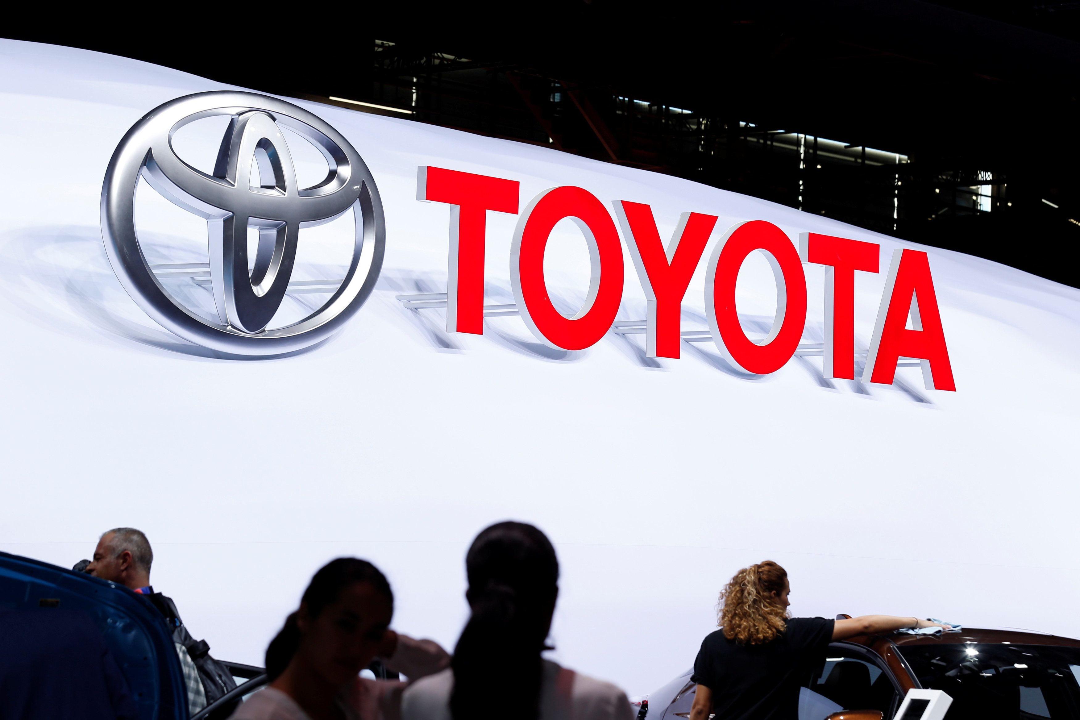 The logo of Japanese car manufacturer Toyota is displayed behind members of the media at the Paris auto show, in Paris, France, September 29, 2016.   REUTERS/Benoit Tessier