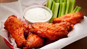 Basket of hot wings with celery sticks and blue cheese dressing.  Please see my portfolio for other food and hot wing images.