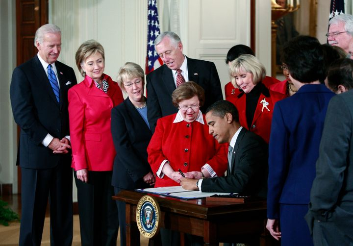 Barack Obama signs the Lilly Ledbetter Fair Pay Restoration Act on January 29, 2009, with Ledbetter standing behind him as he