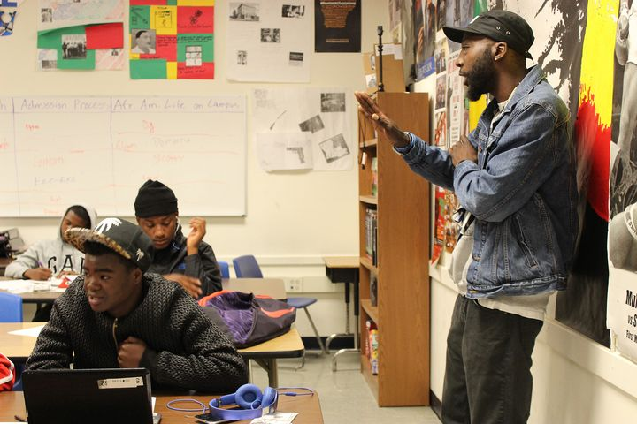 Teacher Earnest Jenkins III assists students with an assignment during his popular Manhood Development class at Oakland High