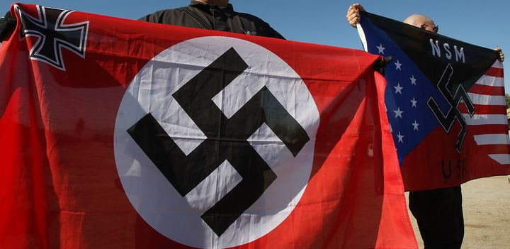 Members of the white supremacist National Socialist Movement hold swastika flags at an anti-immigration rally in Riversi