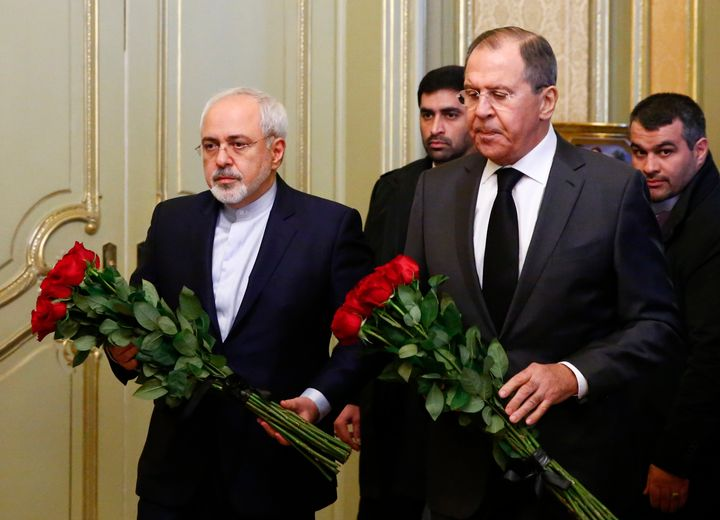 Russian Foreign Minister Sergei Lavrov and his Iranian counterpart Mohammad Javad Zarif lay flowers in front of a photo of a