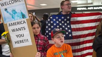Protesters gather at the international arrivals area of the Washington Dulles International Airport on January 28, 2017, in Sterling, Virginia. US President Donald Trump boasted Saturday that his 'very strict' crackdown on Muslim immigration was working 'very nicely,' amid mounting resistance to the order which has been branded by many as blatantly discriminatory. / AFP / PAUL J. RICHARDS        (Photo credit should read PAUL J. RICHARDS/AFP/Getty Images)
