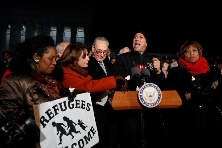 Sen. Cory Booker (D-N.J.), center, speaks at a rally against the travel ban in Washington on Monday.