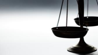 A justice scale on a simple gray background.  The scale is partially silhouetted as a strong backlight obscures some of the finer details.  Scale is place on far right hand side of image leaving ample negative space for copy. Image can be flipped horizontal to accommodate alternative composition needs.